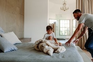 Father and son playing in bedroom