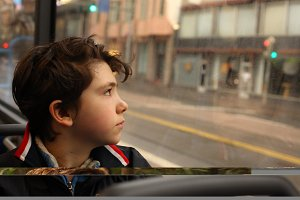 teenager boy in the bus looking at the window