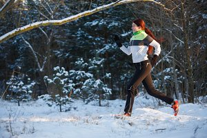 Photo of young athlete running through winter forest