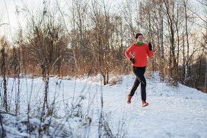Female athlete running in winter park on morning run
