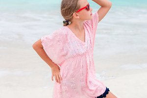 Beautiful little girl in dress at beach having fun. Funny girl enjoy summer vacation.
