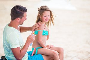 Parent applying sun cream to kid nose. Portrait of lttle girl in suncream