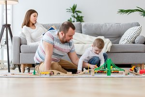 Photo of happy parents with son playing in toy road