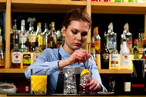 The bartender prepares cocktails at