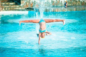 Happy little girl enjoy vacation in the swimming pool. Sporty kid making cartwheel on the edge of pool
