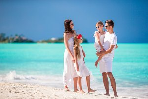 Young family in white on vacation on caribbean beach