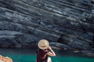 Young girl in a cove on a rock in the Cinque Terre Reserve. Stunning nature, lagoon and fresh air