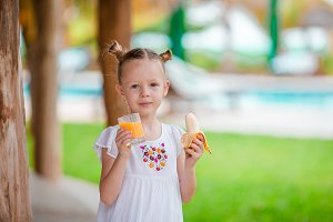 Adorable little girl with fresh juice at outdoor cafe in luxury resort