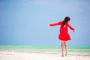 Young beautiful woman in red dress having fun on tropical seashore. Happy girl walking at white sand tropical beach