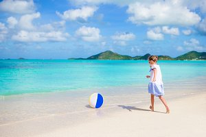 Adorable little girl playing with ball on beach. Kids summer sport outdoors on caribbean island