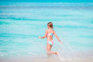 Little happy girl splashing. Kid running to the turquoise water ready to swim