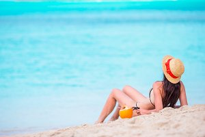 Young woman with coconut in bikini enjoying the sun sunbathing by perfect turquoise ocean.