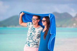 Young couple at tropical beach under the towel hiding from tropical rain. Travel concept