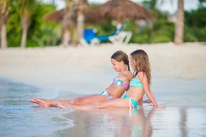 Adorable little girls relaxing on the beach