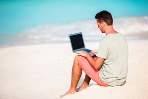 Young man sitting on sand with laptop on tropical caribbean beach. Man with computer and working on the beach