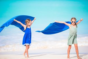 Little girls having fun running with towel and enjoying vacation on tropical beach with white sand and turquoise ocean water