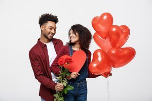 Young attractive african american couple on dating with red rose,heart and balloon.