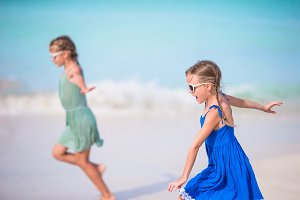 Adorable little girls have a lot of fun on the beach. Two beautiful kids running and splashing in shallow water
