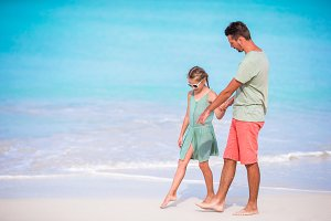 Happy father and his adorable little daughter at tropical beach walking together
