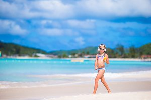 Little girl listening the music by headphones and walking on the beach