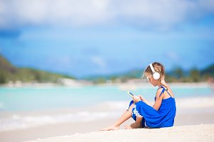 Little girl listening the music by headphones on the beach