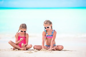 Two little happy girls have a lot of fun at tropical beach playing together with sand