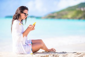 Young woman with smartphone during tropical beach vacation. Beautiful girl on the beach with cellphone on caribbean island