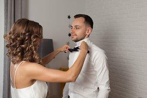 Bride fixes bow tie on groom