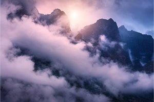 Mountains in clouds in overcast colorful evening