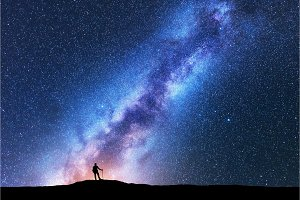 Man with trekking poles and sky with Milky Way