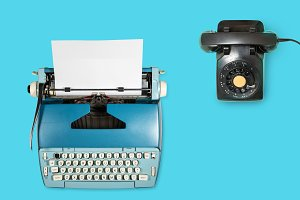 Old electric typewriter and phone on plain background