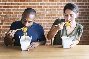Friends eating noodles together