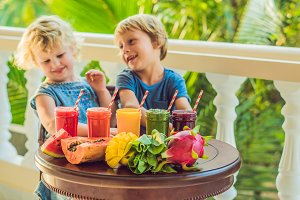 Children drink colorful healthy smoothies.. Watermelon, papaya, mango, spinach and dragon fruit. Smoothies, juices, beverages, drinks variety with fresh fruits on a wooden table
