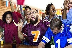 Friends cheering sport at bar