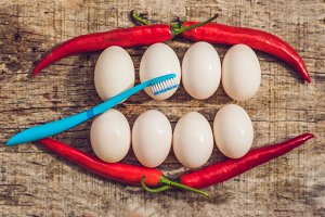 Eggs and peppers in the form of a mouth with teeth and a toothbrush. cleaning the teeth of the concept