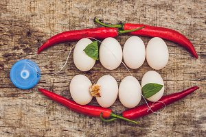Eggs and red peppers in the form of a mouth with teeth. Leaves are stuck to the teeth and dental floss. Cleaning your teeth with dental floss