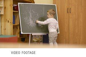 Little boy drawing on a chalkboard