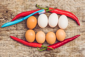 Eggs and red pepper in the form of a mouth with teeth. White eggs are bleached teeth. Yellow eggs - before bleaching. Teeth whitening before and after