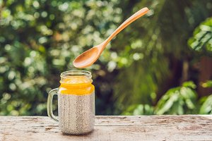 Chia seed pudding with almond milk and fresh mango topping with levitating spoon