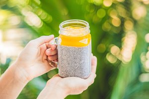 Chia seed pudding with almond milk and fresh mango topping in hand