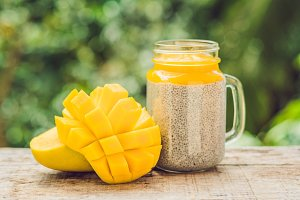Chia seed pudding with almond milk and fresh mango topping on a wooden table
