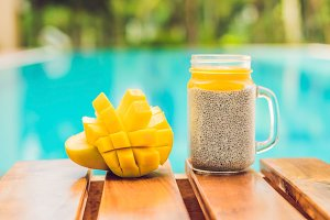 Chia seed pudding with almond milk and fresh mango topping on the background of the pool