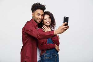 Young attractive African American Couple Pose For selfie pose with smart phone