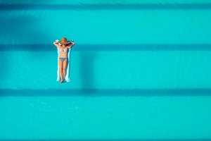 Enjoying suntan. Vacation concept. Top view of slim young woman in bikini on the blue air mattress in the big swimming pool
