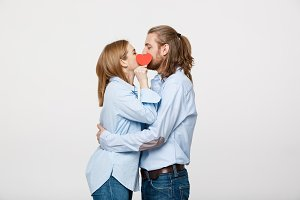 Young attractive couple in blue shirt holding paper heart and kissing.