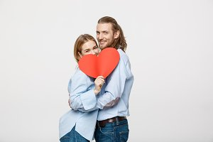 Velentine Concept - Young happy couple in love holding red paper heart