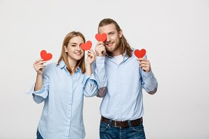 Attractive young in love couple holding red hearts over eyes on white background