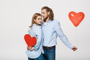 Young attactive caucasian couple holding heart balloon and paper.
