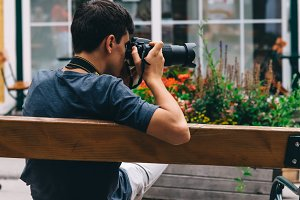 Young adult man taking photos sitting back on bench