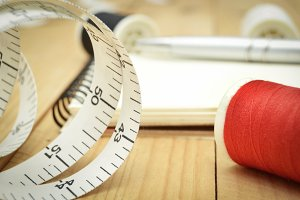 tape measure, thread and notebook